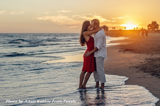 couple on beach abou to kiss with sunset in background