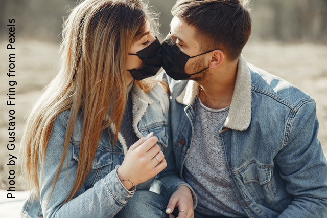 couple wearing masks touching faces