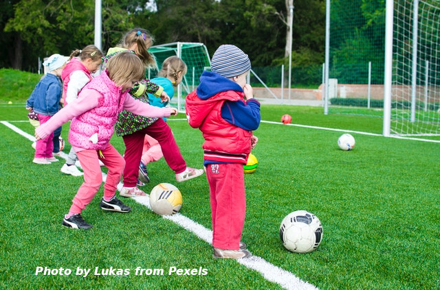 kids playing with ball on soccer field