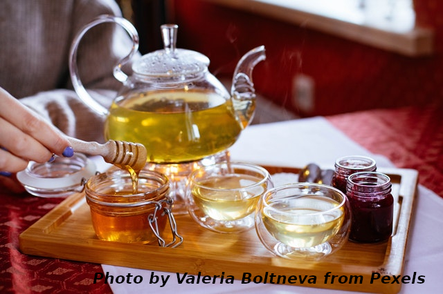 woman pulling honey to pour into tea