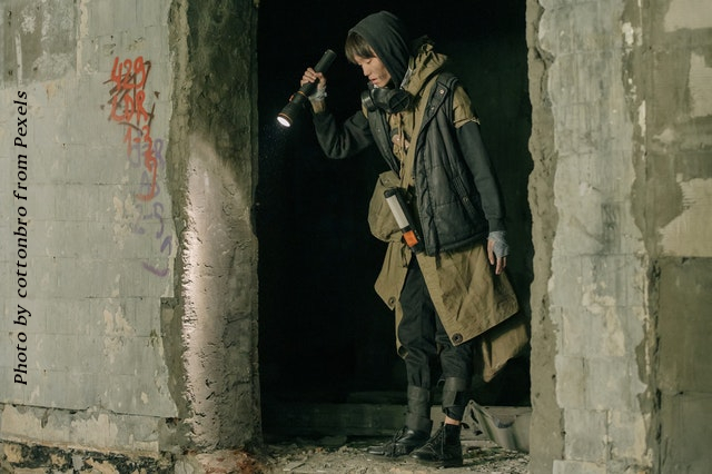 woman wearing black and brown coat in concrete wall opening using flashlight