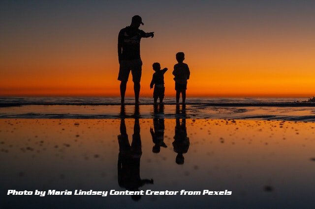 father and soms at seashore sunset