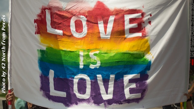 white cloth banner with love is love over LGBTQ colors