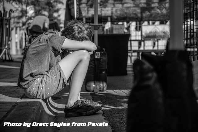 teen sitting on curb with head bowed on knees