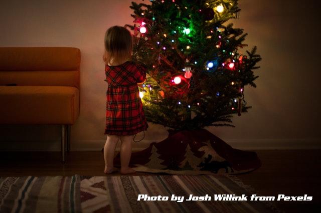 young girl hanging christmas ornaments
